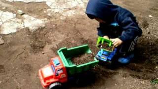 Nene jugando con máquina y camión operativo