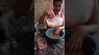 Kenia descacando camarão com apenas uma mão mas utilizando a mao sequelada