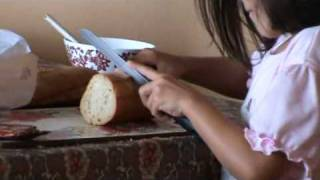 Ani´s little sister trying to cut a piece of bread