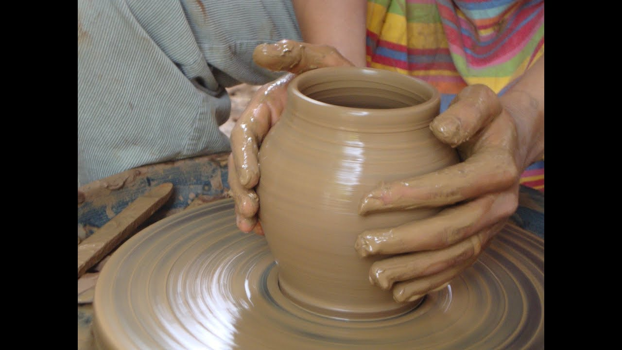 A person makes a work of pottery on a pottery wheel.