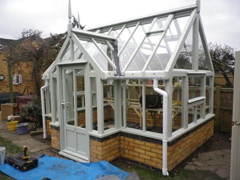 Wooden greenhouse on dwarf brick wall