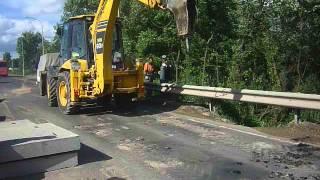 Гидромолот Komatsu WB 93s в Калуге производит демонтаж дорожного полотна.