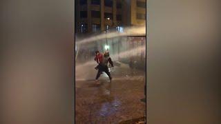 شاهد | قوات الأمن اللبناني تفتح خراطيم المياه باتجاه رجل يحمل طفلاً في بيروت