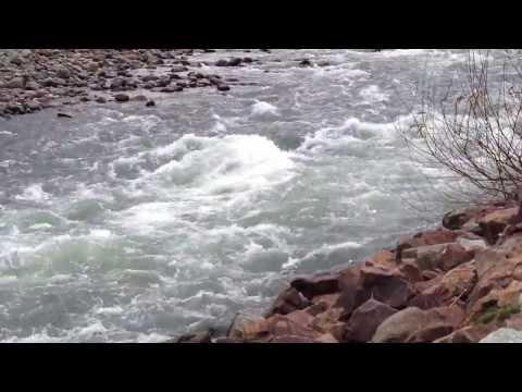 Raging river powers over a group or rocks.