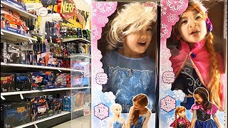 The twins dress up as Elsa and Anna at the Toy Store