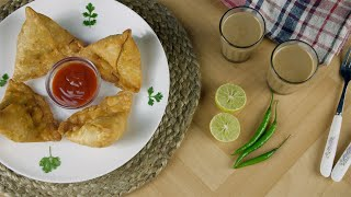 Pan shot of beautifully plated fresh samosas with a bowl of tomato sauce - fast food