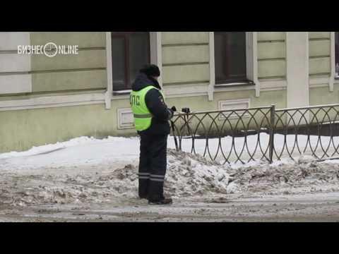 В центре Казани на улице Горького водитель меняет номера за спиной сотрудника ДПС