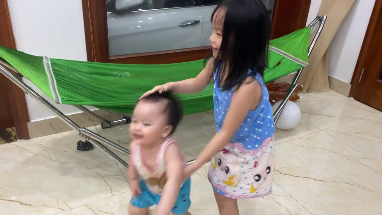 Baby and kids playing balloons with brother in the house