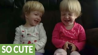 Identical twin babies find kisses hilariously entertaining