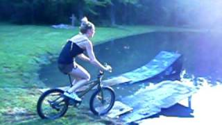 a girly girl jumping off a ramp on a bike into water =)