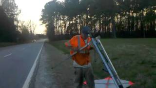 Taking down a road work sign