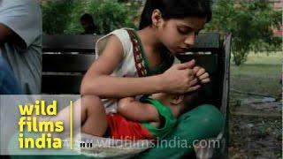 Girl feeding infant with a milk bottle