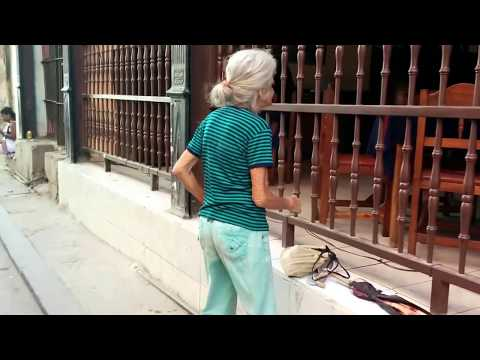 old woman dancing to music in street of Havana