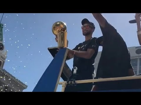 Steph Curry holds the Championship trophy as the golden state warriors roll through oakland