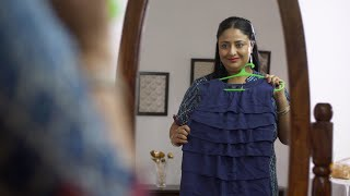 Overweight Indian woman desiring to wear her dress - obesity concept