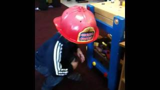 Wearing a fireman hat playing with a hammer