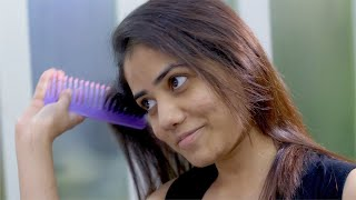 Shot of an Indian girl combing her hair and smiling
