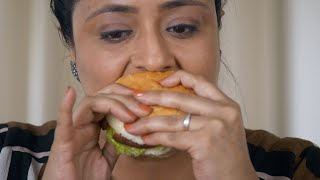Indian woman eating high-calorie food, Vegetable burger - Health risk concept