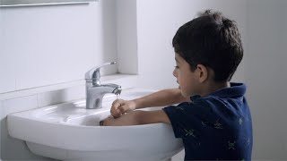 Slow motion shot of a cute Indian boy washing his hands in the washbasin
