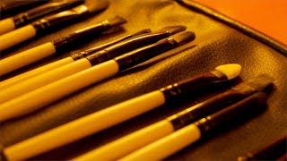 A beautiful collection of makeup brushes spread on a leather mat - Indian Beauty Parlor