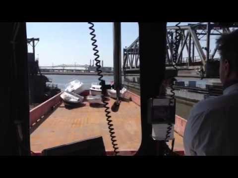 Tug pushes barge through bridge