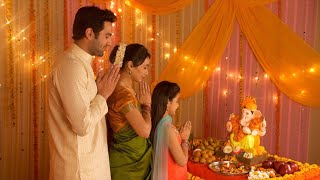 Nuclear Indian family worshiping Lord Ganesha during festivities - Ganesh Chaturthi