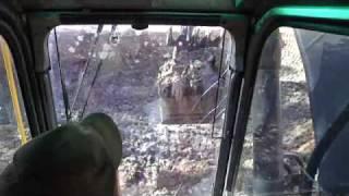 Excavator loading mud into Dump Truck
