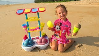 Kid and Dolls Pretend Play with colored Ice Cream Toys and cakes from sand on the Beach
