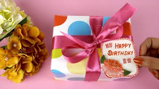 Top view shot of beautiful flowers and a colorful birthday present - pink background