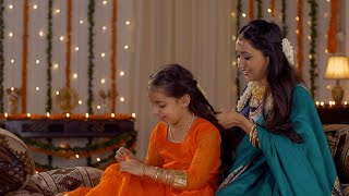 South Indian mother wearing traditional dress is helping her daughter with hairstyle - Festival at Home