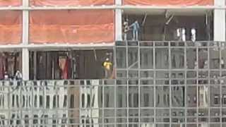 Harnessed Manhattan construction workers install window in high-rise