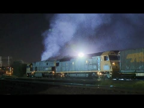 Smokey Pacific National Locomotives with a long freight train in Melbourne.