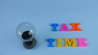 "A sand clock flowing next to the ""Tax Time"" words composed with plastic letters"