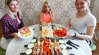 Russian Girls Eating Swiss Raclette. Melted Cheese over Grilled Meat