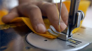 Hands of a female worker putting a yellow coloured textile to a sewing machine