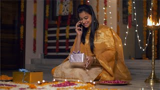 Beautiful Indian girl talking on phone with Diwali gift in her lap