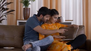 Young Indian couple looking at the laptop sitting on the couch. Shopping online for their new home interiors