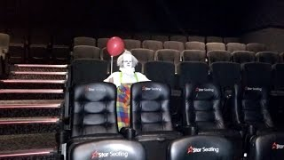 clown dressed as pennywise sits alone in movie theater before showing of it