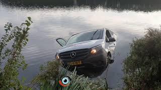 Bedrijfsbus glijdt in het water in Spijkenisse
