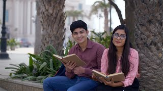 College scene of Indian teenagers sitting together and smiling looking at the camera