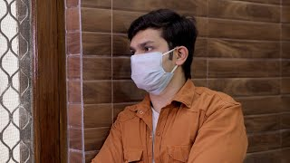 A young attractive boy looks out of the window while wearing a surgical mask