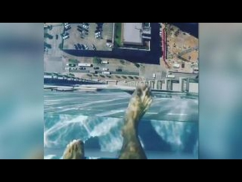 Swimming over the edge in glass bottom pool 40+ floors high
