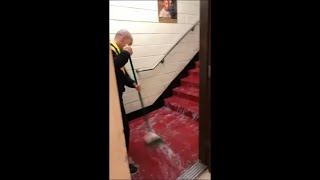 Guy Trying to Shove the Flood Water Out While Singing
