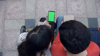Overhead shot of a young boyfriend girlfriend using a green screen mobile phone