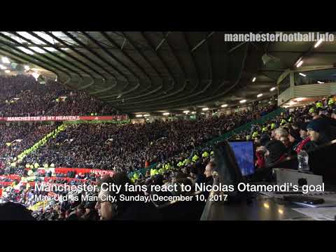 Manchester City fans at Old Trafford celebrate Nicolas Otamendi's goal