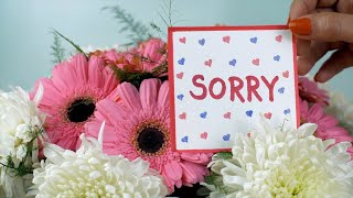 A sorry message card with a bouquet of pink and white flowers - blue background