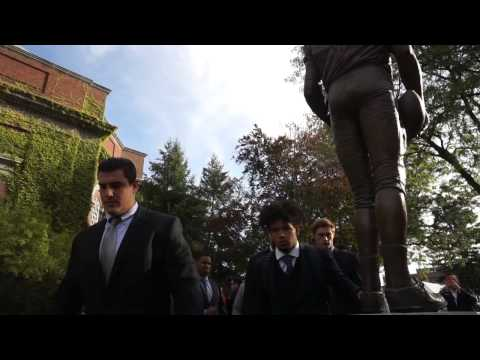 Syracuse football players touch Ernie Davis statue as part of pregame ritual