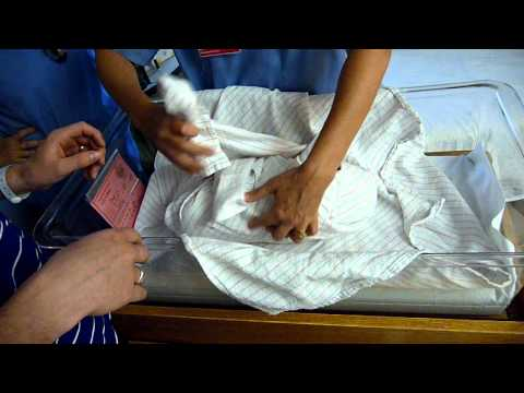 Nurse teaching how to swaddle a newborn