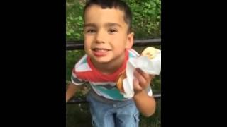 Little cute kid having the best hot dog ever