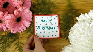 Woman hands placing a Happy Birthday greeting card on a decorated wooden surface